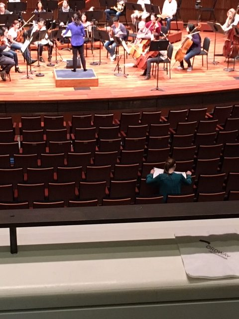 Maya follows along with her score during rehearsal in St. Paul, MN - 2018.