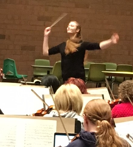 Portrait photograph of Maya Miro Johnson conducting orchestra in 2017.