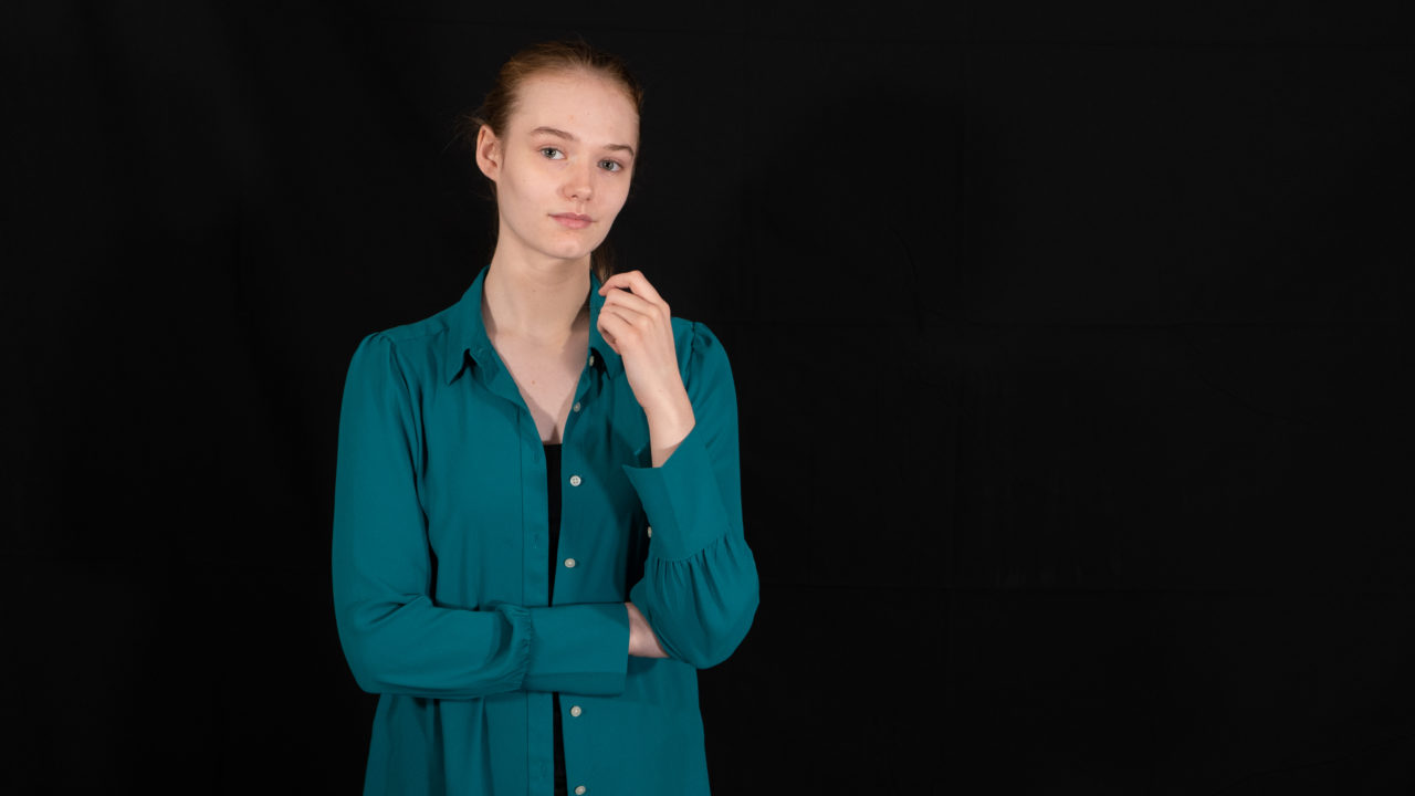 Portrait photograph of Maya Miro Johnson in 2018 with green shirt.